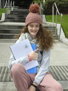 Image of young person in track suit with beanie on holding school books