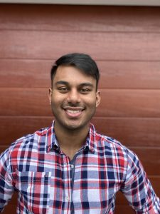 Image of young man, Jahin Tanvir, in red and blue plaid shirt with a plain wooden wall background