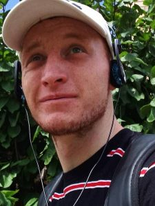 Image of person, Ryan, with striped t short and white cap on, wearing headphones and looking up into the distance.
